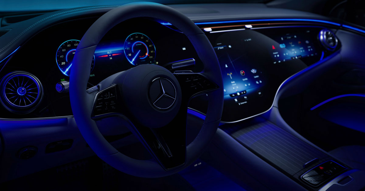 A picture of the Mercedes-Benz EQS steering wheel in the dark featuring ambient lighting